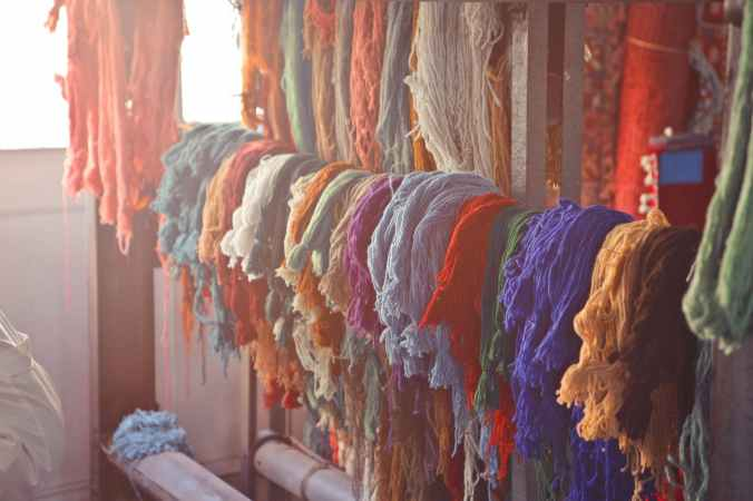 various colorful threads hanging on rail in workshop
